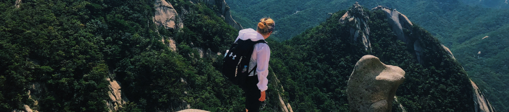Girl stands on green mountain with her back to the camera
